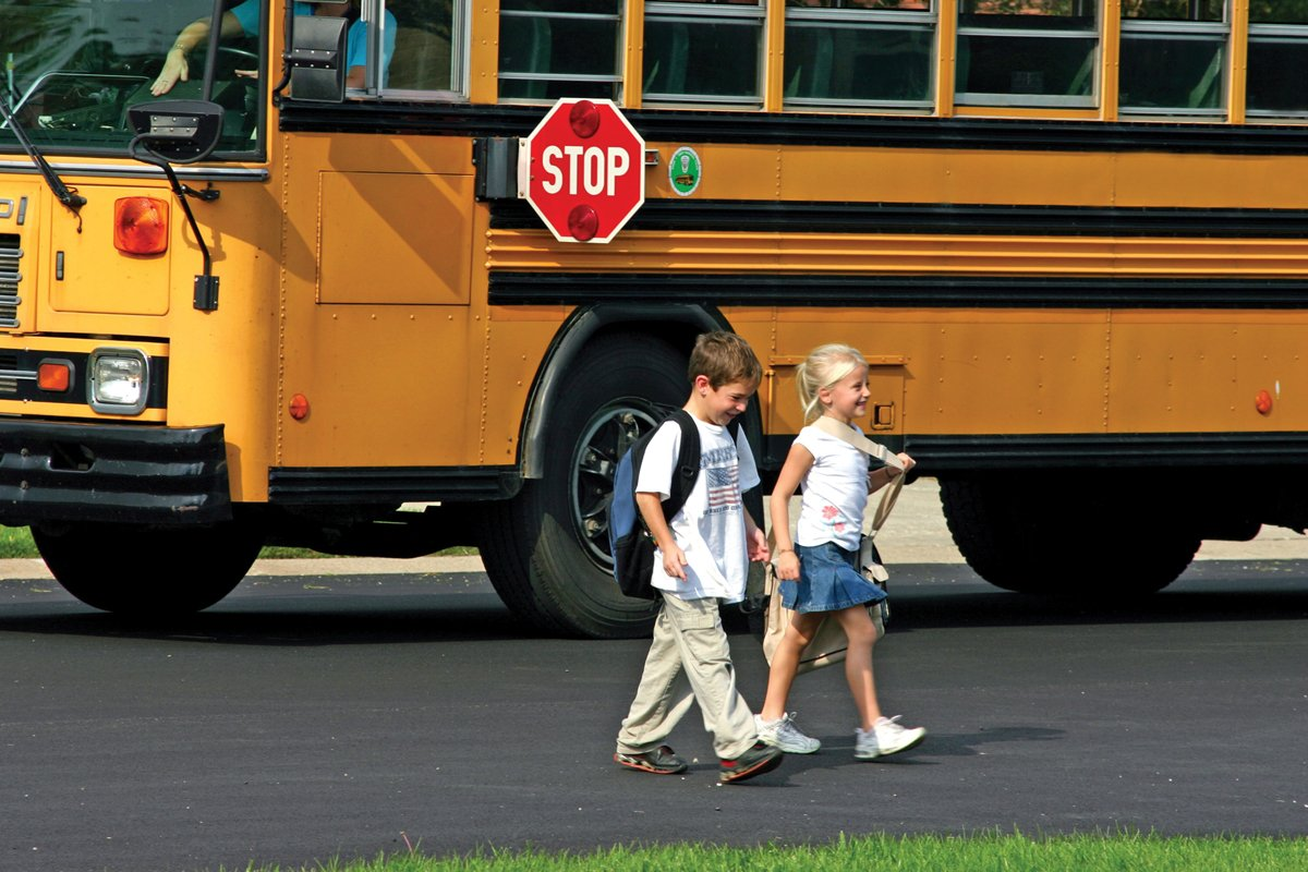 Two children departing from stopped school bus.