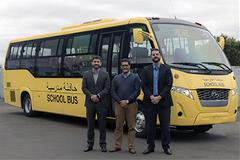 Three people standing in front of bus in Dubai.